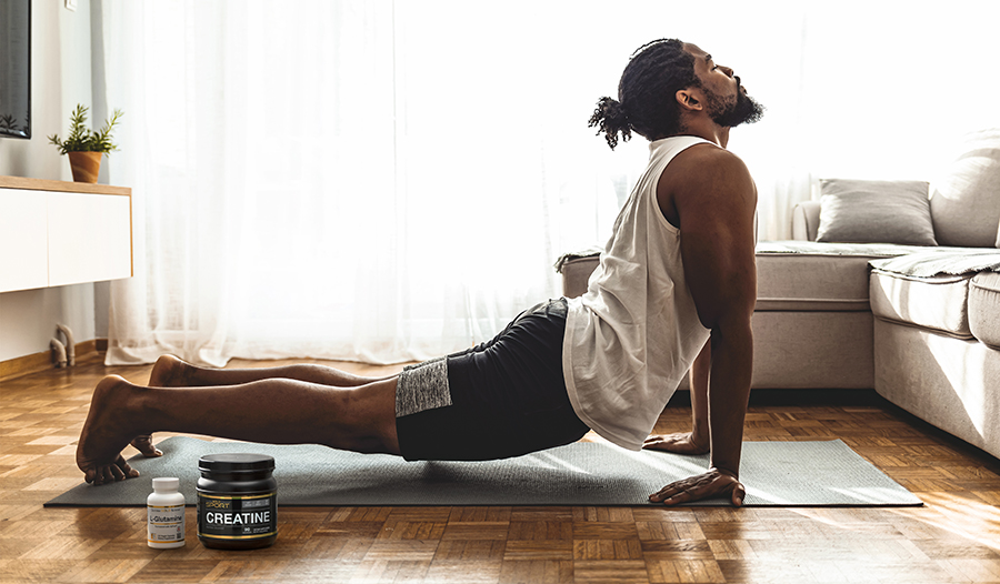 Male doing yoga on the floor in living room with sports supplements