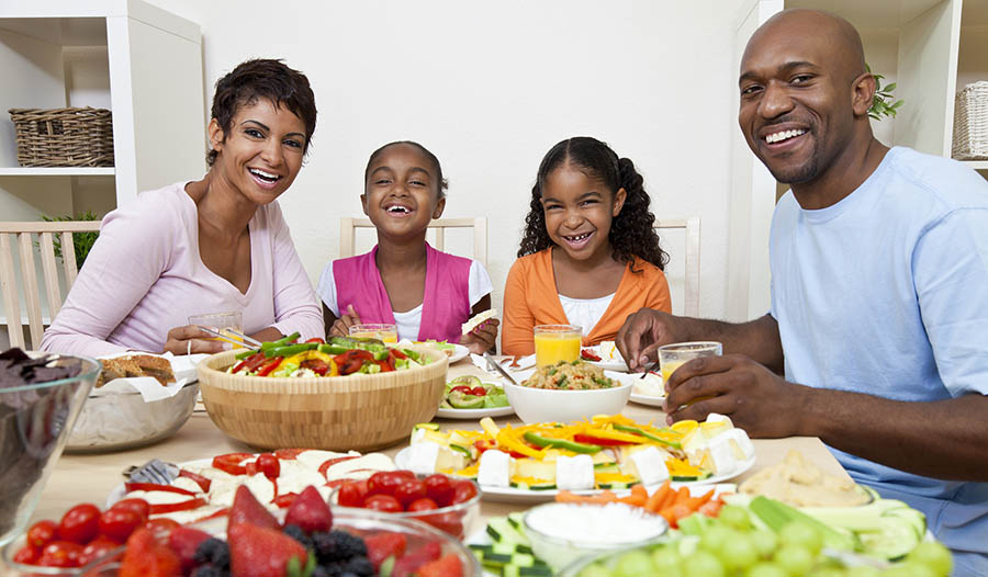 Family sitting at table eating healthy meal together