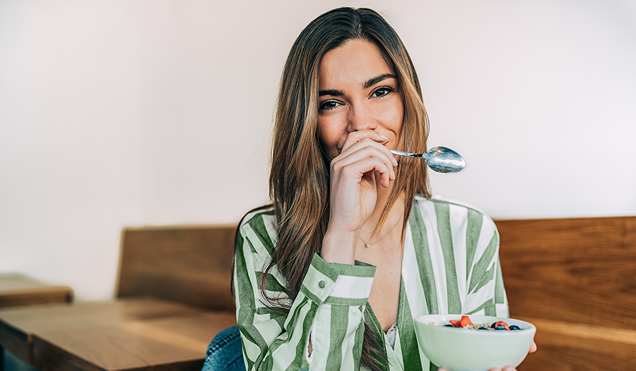 Young woman eating a healthy snack of yogurt and oats