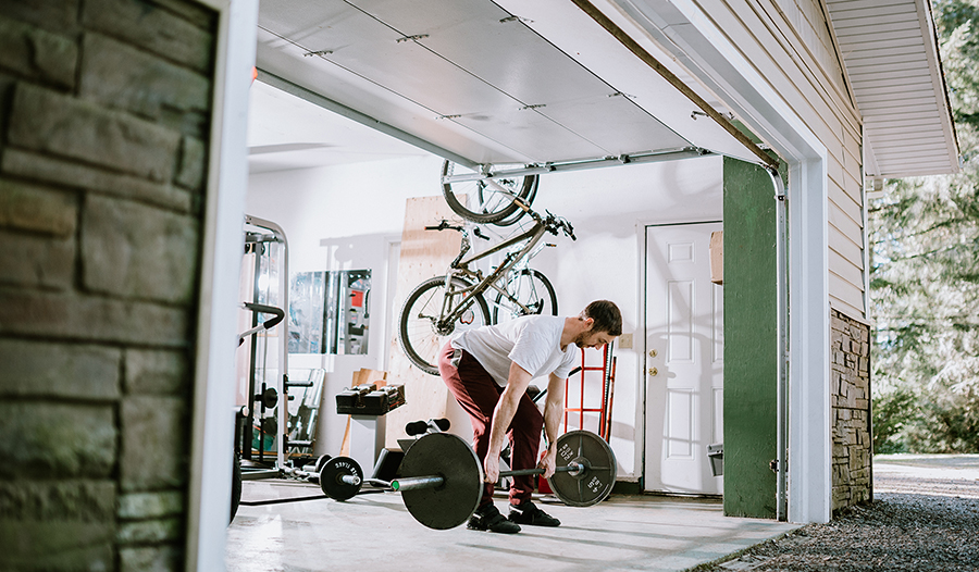A man working out and lifting weights in his home garage.