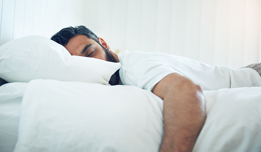 Brunette man with beard asleep in bed with white sheets
