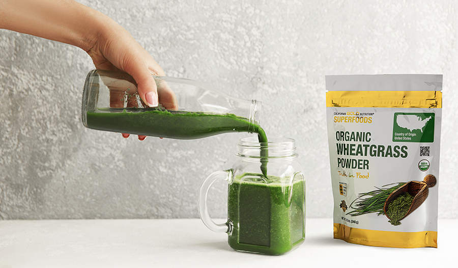 Green juice smoothie poured in a mason jar with wheatgrass powder package on table