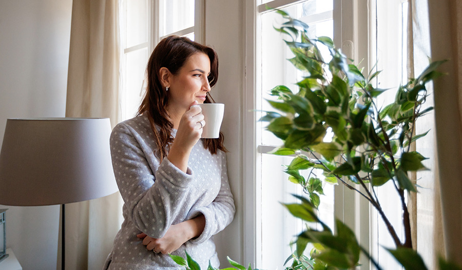 Brunette woman drinking coffee in the morning looking out the window