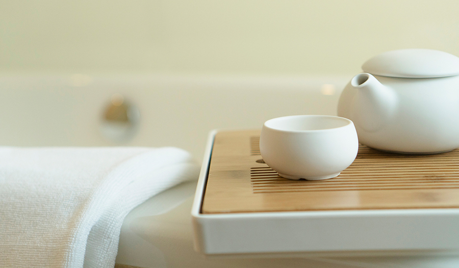 white teapot and teacup on a wooden tray next to a towel resting on the edge of a bathtub