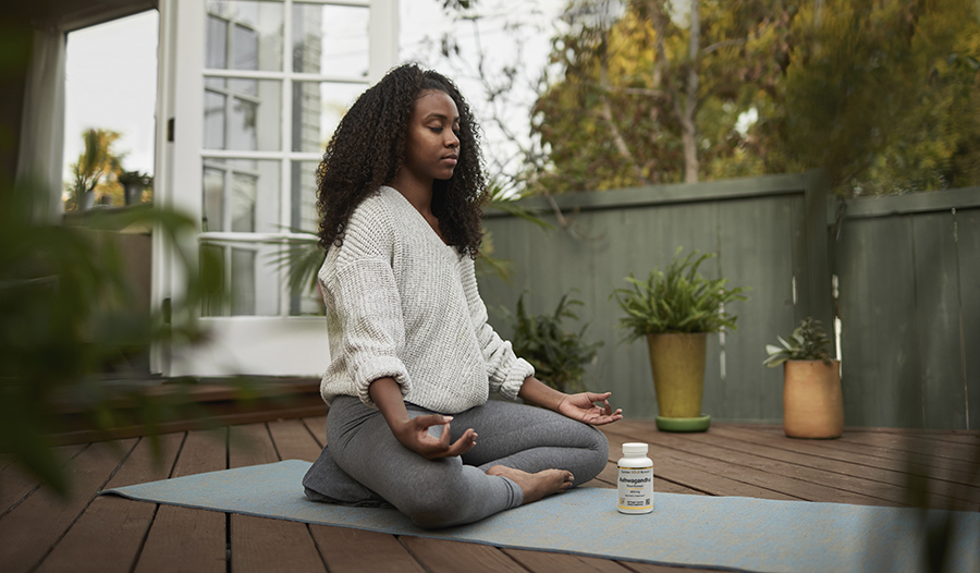 Young woman meditating outside in the garden on yoga mat
