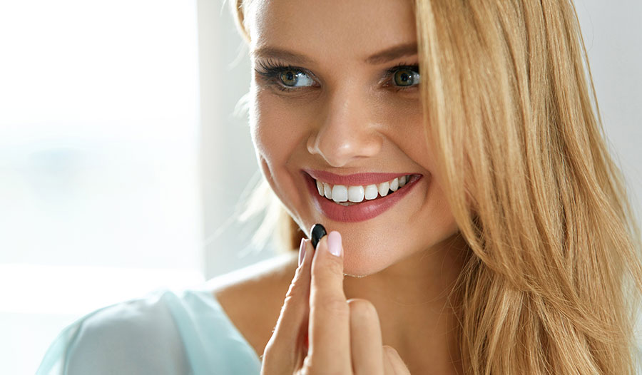 woman taking a beauty supplement with vitamins and minerals for healthy hair, skin and nails