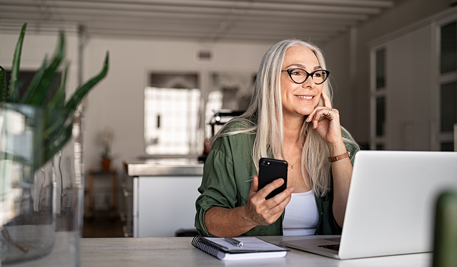 Happy senior woman with smartphone and laptop working from home