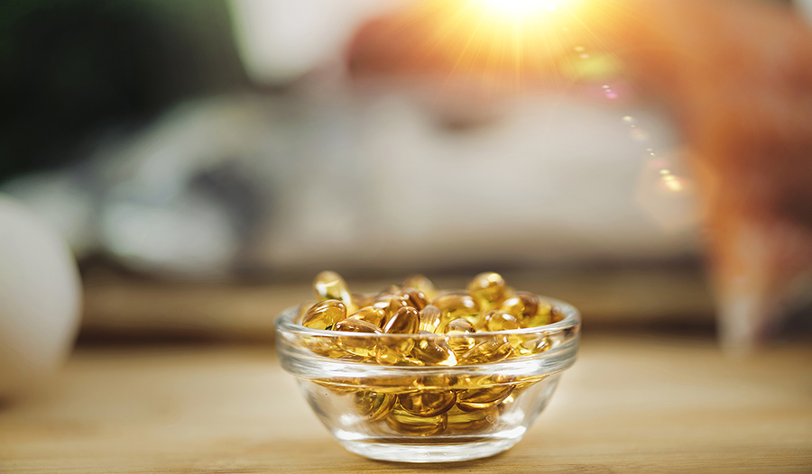 Fish oil supplements in glass bowl on table with sun in the background