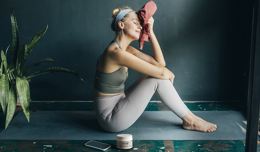 Woman taking a break after working out wiping sweat with towel