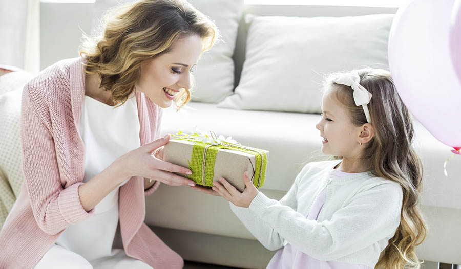 Daughter giving gift to mother on Mother's Day