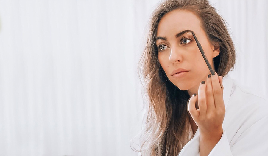 celebrity makeup artist in a white bathrobe applying a brow pencil to her eyebrow