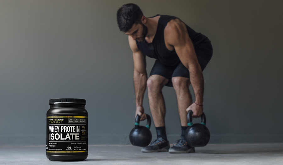 Male athlete exercising with kettlebells with whey protein