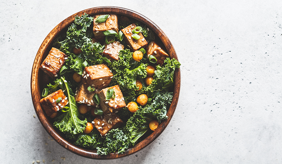 Teriyaki tofu salad with kale and chickpeas in a wooden bowl on white background