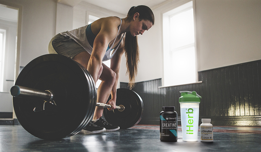 Fit woman lifting weights in the gym with sports supplements and water bottle