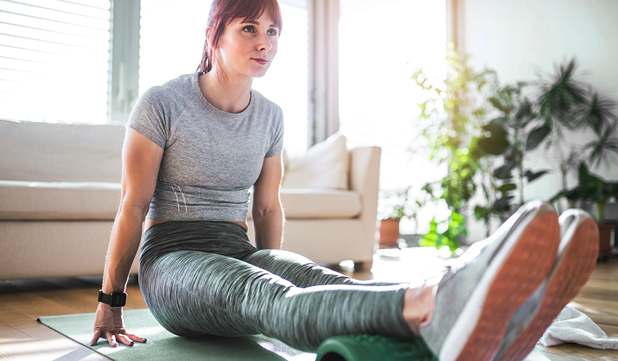 Young active woman using foam roller at home