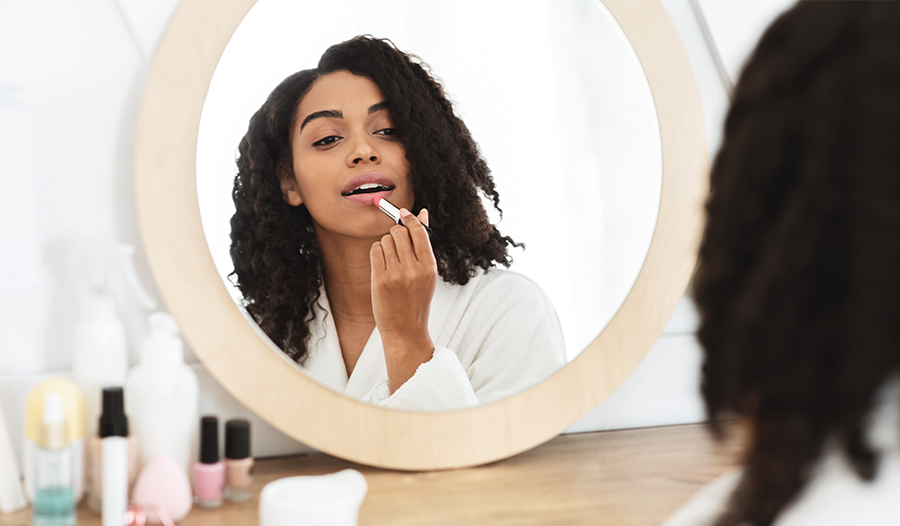 woman applying lipstick from her makeup bag in the mirror