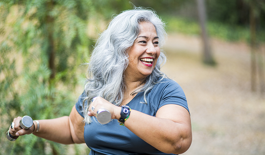 Healthy happy mature woman exercising outside with light weights