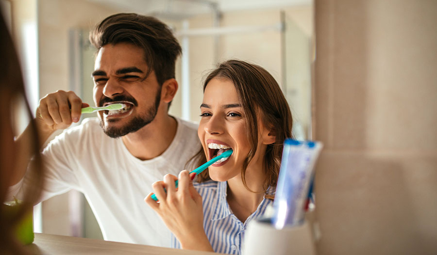a couple brushing their teeth in the mirror based on their revamped oral care routine
