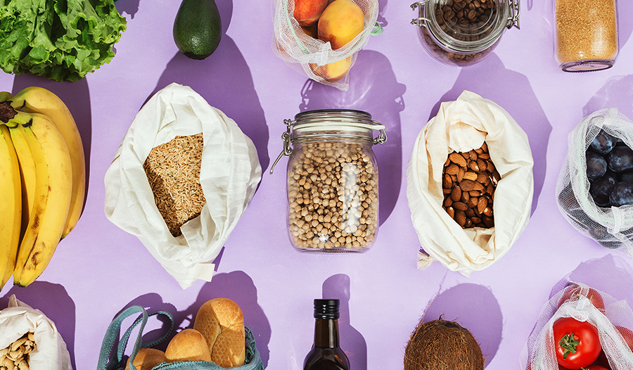 Healthy nuts, seeds, and grocery items on a purple background