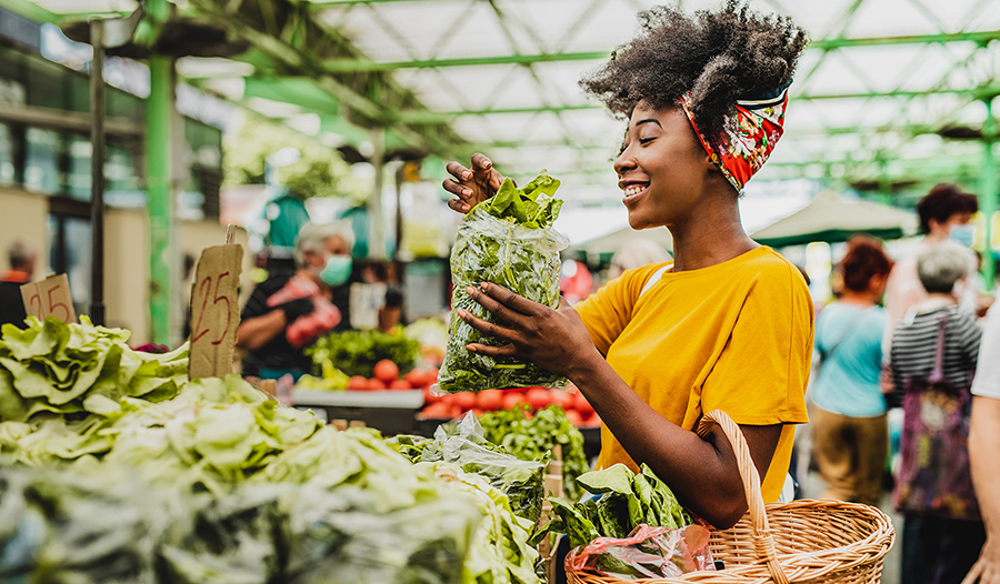 Healthy young black woman holding a basket full of groceries at the farmers market