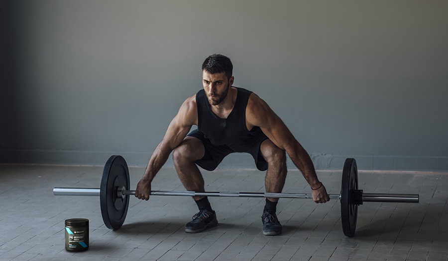 Male athlete lifting barbell with pre-workout supplement on floor