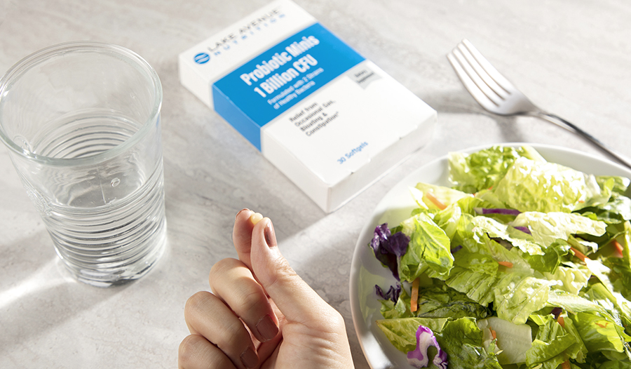 Probiotics on white marble table with salad and glass of water
