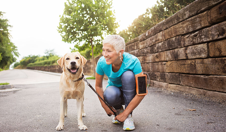 woman bending down smiling at her dog outdoors