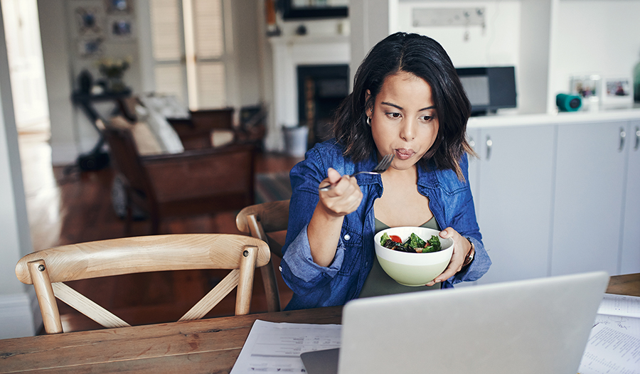 Young woman working at kitchen table eating a salad for lunch
