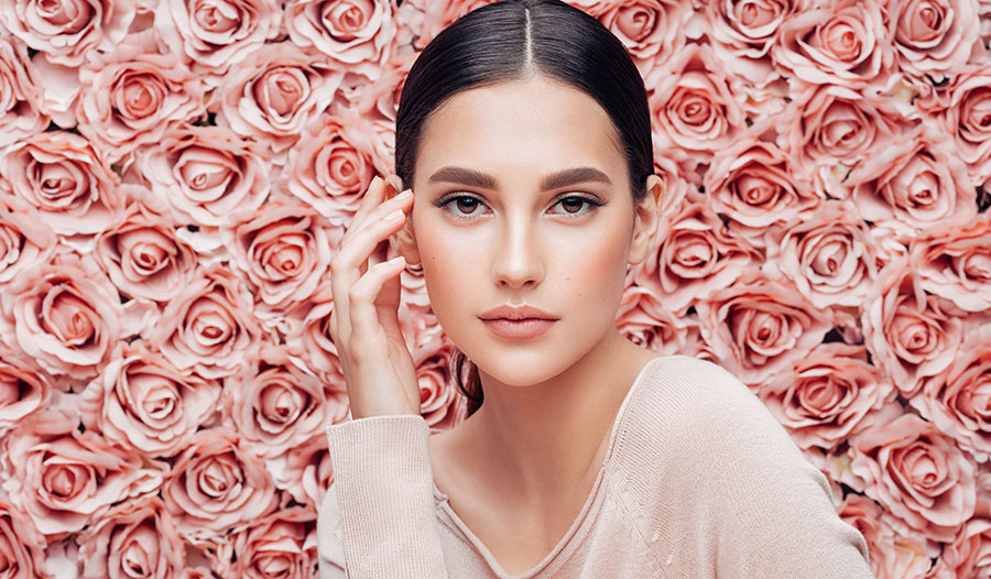 woman thinking about rose-infused beauty products in front of a wall of pink roses