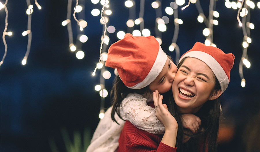 mom practicing self care by giving daughter piggy back ride wearing santa hats with holiday lights a