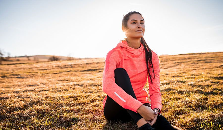 woman sitting in a field by herself practicing self-care mantras