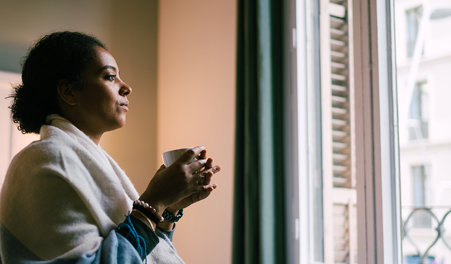 Woman wrapped in blanket with cup of tea looking out the window