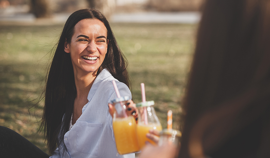 Young woman toasting with orange juice in the park