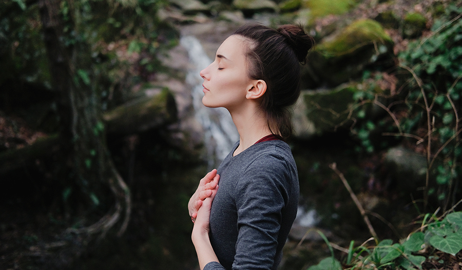 Young woman breathing deeply outdoors in front of waterfall