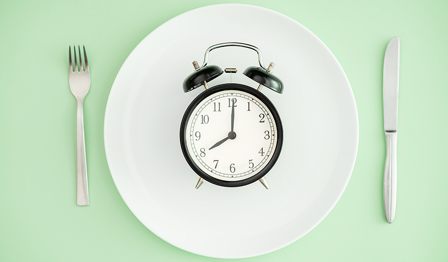 Intermittent fasting concept of alarm clock on plate on green background