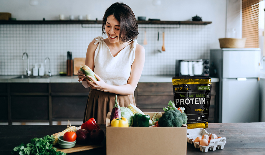 Asian woman unpacking healthy groceries in kitchen with vegan protein powder, vegetables, and eggs o