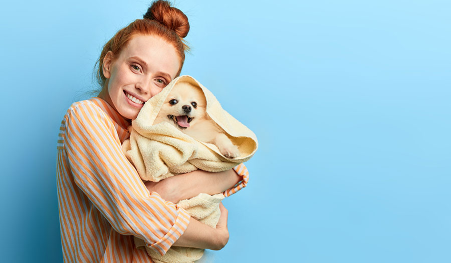 woman holding a puppy wrapped in a towel