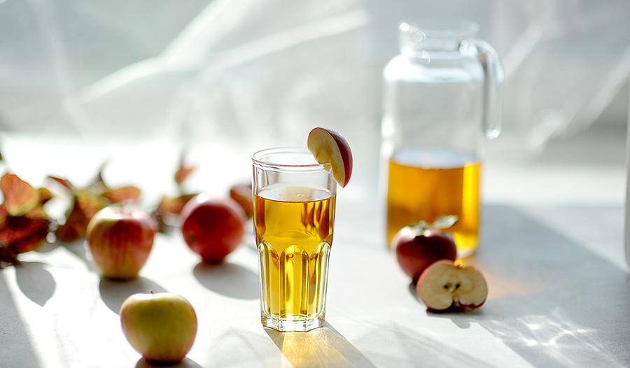 Apple cider vinegar wellness shot in glass on white background with apples and pitcher.