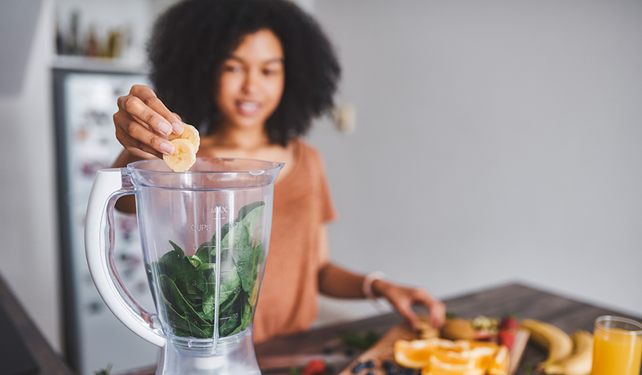 Young woman making a healthy smoothie at home