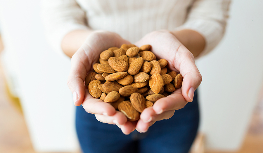 Young woman holding almonds in her hands
